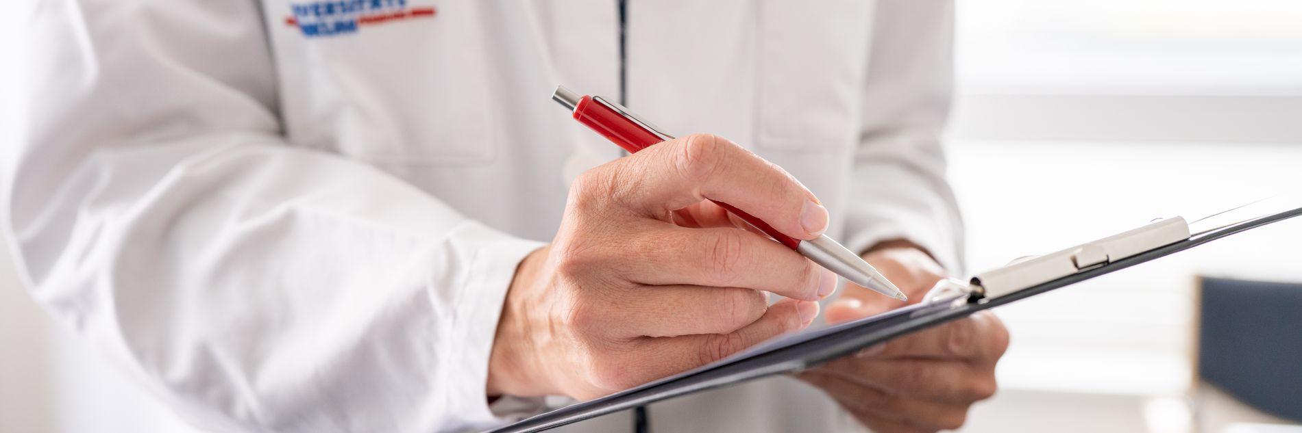 Arzt macht Notizen auf Klemmbrett